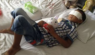 Guo Bin recuperates in a hospital in Taiyuan in northwest China's Shanxi province on Wednesday, Aug. 28, 2013, from an attack in the rural area of Linfen city that left him blind. A woman tricked the 6-year-old boy into going into a field, and then gouged out his eyes, police said. (Associated Press)