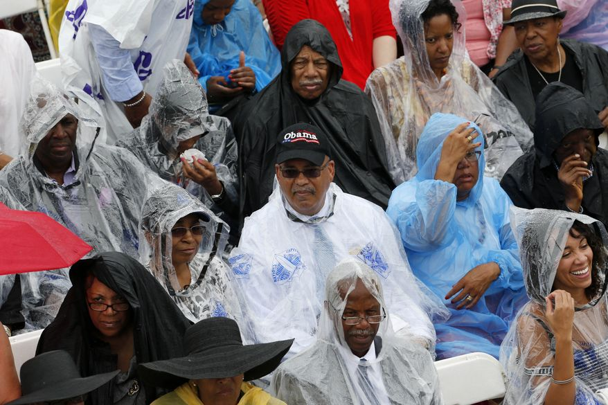 Audience members sit in rain for the 50th Anniversary of the March on Washington, Wednesday, Aug. 28, 2013, in front of the Lincoln Memorial in Washington, where Martin Luther King, Jr. spoke. President Barack Obama is scheduled to speak later in the day. (AP Photo/Charles Dharapak)
