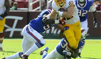 Redskins' tight end Logan Paulsen (82) tries to break the tackle of the Bills defenders after catching a pass and running for a first down during their NFL preseason football game, Saturday, Aug. 24, 2013, in Landover, Md. Redskins defeated the Bills 30-7. (AP Photo/Richard Lipski)