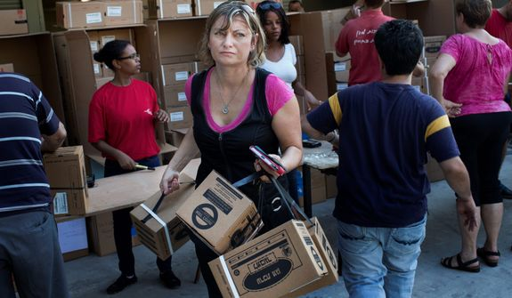 An Israeli woman carries gas masks at a distribution center in the northern port city of Haifa, Israel, Thursday, Aug. 29, 2013. Israeli police say thousands of Israelis are crowding gas mask distribution facilities, readying for a potential conflict in Syria. (AP Photo/Bernat Armangue)