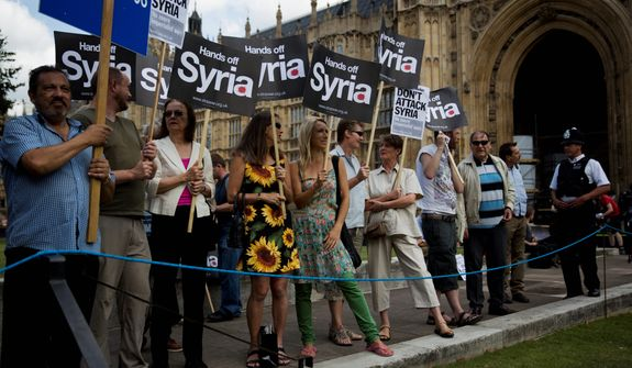 People take part in a protest calling for no military attack on Syria from the U.S., Britain or France, outside the Houses of Parliament, in London, organized by the Stop the War coalition and timed to coincide with a debate and vote by politicians, Thursday, Aug. 29, 2013.  Britain's leaders said Thursday it would be legal under humanitarian doctrine to launch a military strike against Syria even without authorization from the United Nations Security Council.  Prime Minister David Cameron's office said the legal conditions have been met for taking action against Syria for allegedly launching a chemical attack against civilians in a Damascus suburb last week.  (AP Photo/Matt Dunham)