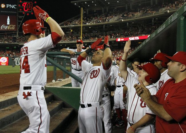 Washington Nationals outfielder Bryce Harper, left, celebrates his fourth-inning home run with shortstop Ian Desmond and the rest of his teammates in the Nationals' 9-0 victory over the Marlins. (Associated Press photo)