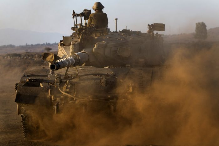 Israeli soldiers drive a tank at a staging area in the Golan Heights, near the border between the Israeli-controlled Golan Heights and Syria, on Aug. 29, 2013. United Nations experts are investigating the alleged use of chemical weapons in Syria as the United States and allies prepare for the possibility of a punitive strike against President Bashar Assad's regime, blamed by the Syrian opposition for the attack. The international aid group Doctors Without Borders says at least 355 people were killed in the Aug. 21 attack. (Associated Press)