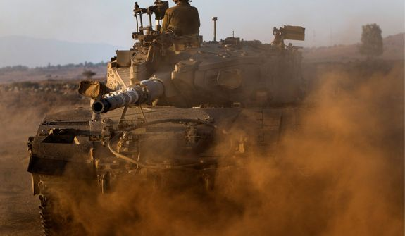 Israeli soldiers drive a tank at a staging area in the Golan Heights, near the border between the Israeli-controlled Golan Heights and Syria, Thursday, Aug. 29, 2013. United Nations experts are investigating the alleged use of chemical weapons in Syria as the United States and allies prepare for the possibility of a punitive strike against President Bashar Assad's regime, blamed by the Syrian opposition for the attack. The international aid group Doctors Without Borders says at least 355 people were killed in the Aug. 21 attack. (AP Photo/Bernat Armangue)
