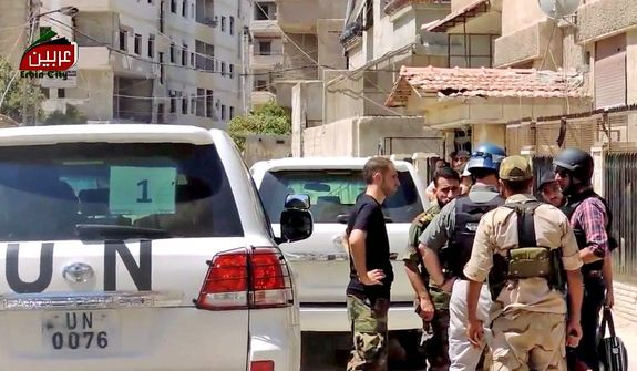 In this image taken from video obtained from the Erbin Ciity, which has been authenticated based on its contents and other AP reporting, U.N. investigation team with blue helmets speak with Free Syrian Army fighters in the Damascus countryside of Zamalka, Syria, Thursday, Aug. 29, 2013. Syria's state news agency quoted President Bashar Assad as saying Syria will defend itself against any aggression. (AP Photo/Erbin City via AP video)