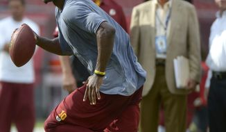 Washington Redskins team physician Dr. Tony Casolaro, right, surgeon Dr. James Andrews, second from right, and team television analyst Joe Theismann watch as quarterback Robert Griffin III, foreground, warms up before a preseason NFL football game against the Tampa Bay Buccaneers in Tampa, Fla., Thursday, Aug. 29, 2013.(AP Photo/Phelan M. Ebenhack)