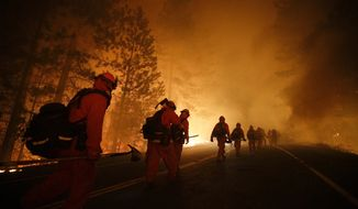 Inmate firefighters walk along Highway 120 after a burnout operation as firefighters continue to battle the Rim Fire near Yosemite National Park, Calif., on Sunday, Aug. 25, 2013. Fire crews are clearing brush and setting sprinklers to protect two groves of giant sequoias as a massive week-old wildfire rages along the remote northwest edge of Yosemite National Park. (AP Photo/Jae C. Hong)