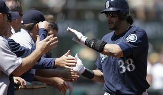 Seattle Mariners' Michael Morse (38) is congratulated after hitting a home run off Oakland Athletics' A.J. Griffin in the second inning of a baseball game on Wednesday, Aug. 21, 2013, in Oakland, Calif. (AP Photo/Ben Margot)
