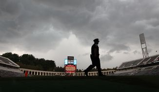 A University of Virginia police officer patrols Scott Field after lightning from a storm caused officials to evacuate the stadium during the first half of an NCAA college football game football game, Saturday, Aug. 31, 2013 in Charlottesville, Va. (AP Photo/The Progress-Index, Andrew Shurtleff)