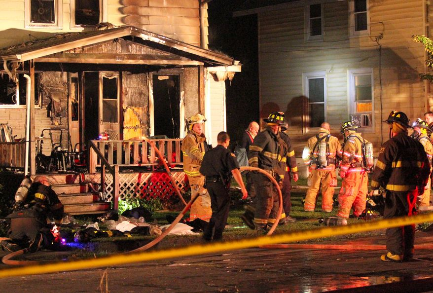 Police and firefighters work at the site of a house fire that killed four people in Elmira, N.Y., on Friday, Aug. 30, 2013. Police say firefighters pulled four victims from the building and took them to the hospital, but none survived the night. The cause was under investigation. (AP Photo/Elmira Star-Gazette, Ron Levanduski)
