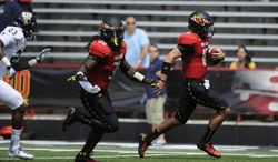 Maryland quarterback C.J. Brown, right, heads for the end zone en route for a touchdown as teammate Kenneth Goins Jr., center, provides blocking against Florida International safety Terrance Taylor (23) during the first half of an NCAA football game, Saturday, Aug. 31, 2013, in College Park, Md. (AP Photo/Nick Wass)
