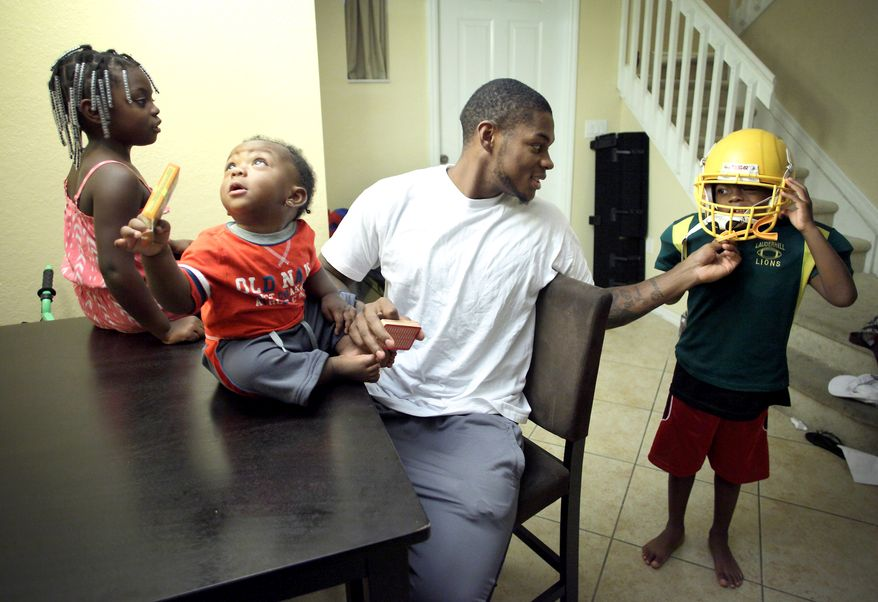 Washington Redskins wide receiver Leonard Hankerson, centers, helps his child Leonard, 7, right, to wear a football helmet at their home in Lauderhill, Florida on July 18, 2013. Next to Hankerson are his daughter Kienarria, 4, left, and son Lenaris, 11 month old. (Cristobal Herrera/For The Washington Times)