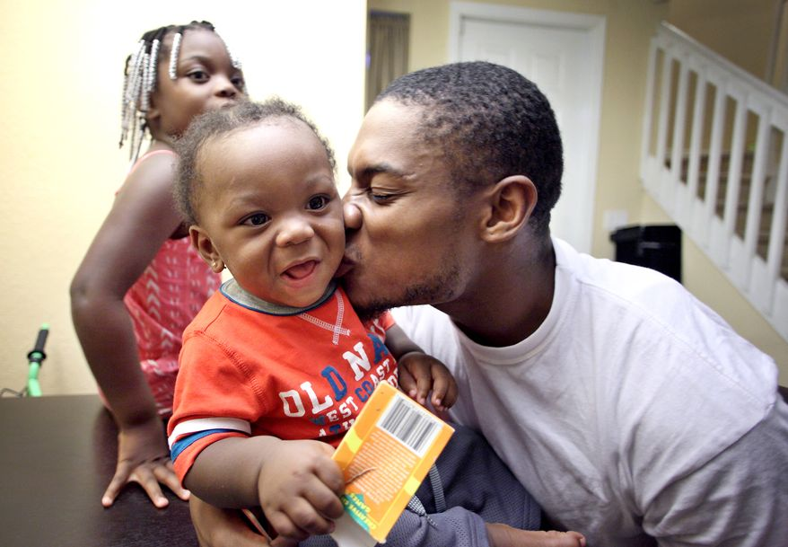 Washington Redskins wide receiver Leonard Hankerson kisses his 11 month-old son Lenaris at their home in Lauderhill, Florida on July 18, 2013. Next to Hankerson is his daughter Kienarria, 4. (Cristobal Herrera/For The Washington Times)