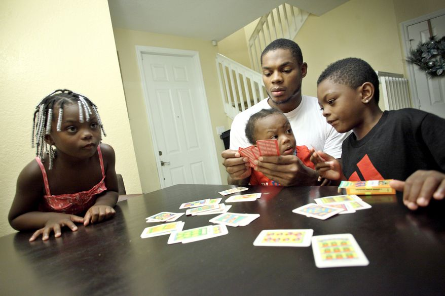 Washington Redskins wide receiver Leonard Hankerson, center, plays with his kids Leonard, 7, Kienarria, 4,  and Lenaris, 11 month old at their home in Lauderhill, Florida on July 18, 2013. (Cristobal Herrera/For The Washington Times)