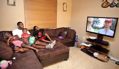 Washington Redskins wide receiver Leonard Hankerson, center, watches TV with his kids Leonard, 7, Kienarria, 4, left, and Lenaris, 11 month old at their home in Lauderhill, Florida on July 18, 2013. (Cristobal Herrera/For The Washington Times)