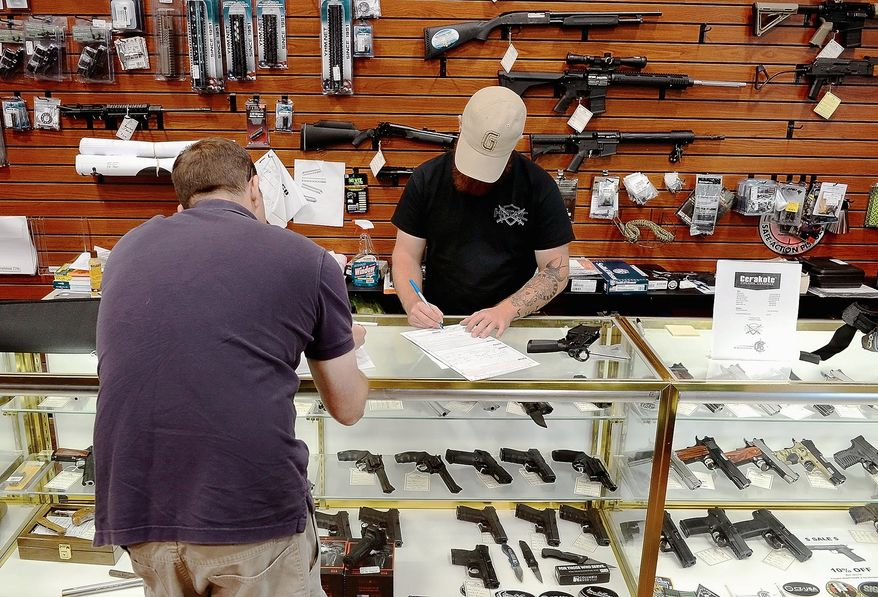Hendershot's Sporting Goods sales associate Robbie Wood (right) fills out the paperwork for a customer for a regulated firearm transfer at the National Pike store east of Hagerstown, Md. (Ric Dugan/The (Hagerstown) Herald-Mail) **FILE**