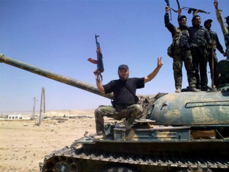 Free Syrian army fighters hold their weapons as they stand on a military tank in Idlib province, Syria, Wednesday, Sept. 4, 2013. (AP Photo/Aleppo Media Center, AMC)