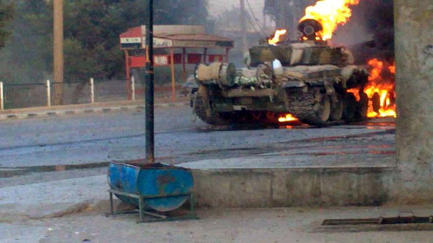 A Syrian military tank is aflame during clashes with Free Syrian Army fighters in Joubar, a suburb of Damascus, Syria, on Wednesday, Sept. 4, 2013, in this citizen journalism image provided by the Syrian Revolution Against Bashar Assad and authenticated based on its contents and other AP reporting. (AP Photo/The Syrian Revolution Against Bashar Assad)