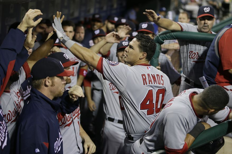 Washington Nationals catcher Wilson Ramos gets high fives in the dugout after hitting a three-run home run in the second inning Tuesday night. (Associated Press photo)
