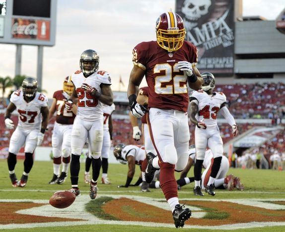 Washington Redskins running back Evan Royster (22) scores past the Tampa Bay Buccaneers defense, including Leonard Johnson (29) and Ahmad Black (43), on a one-yard touchdown run during the first quarter of an NFL preseason football game, Thursday, Aug. 29, 2013, in Tampa, Fla. (AP Photo/Brian Blanco)