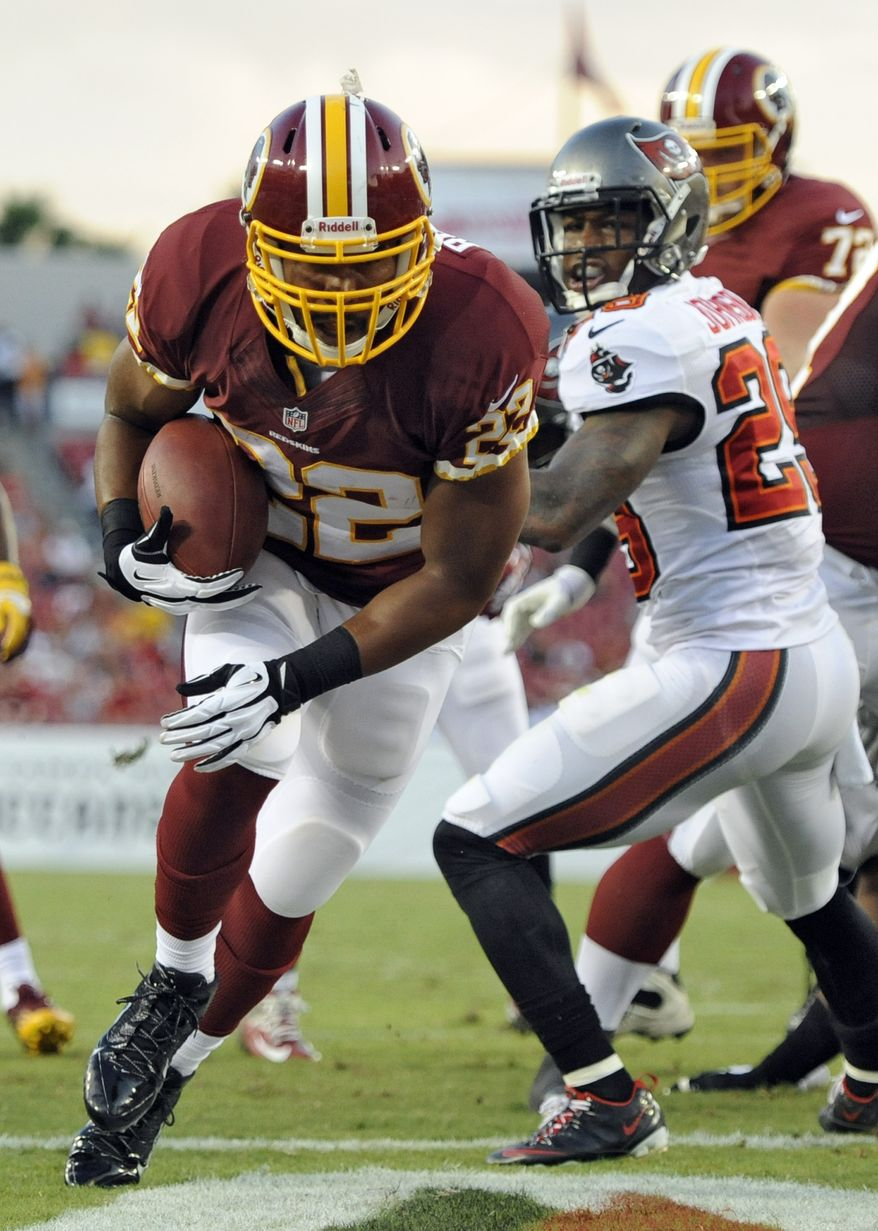 Washington Redskins running back Evan Royster (22) scores past Tampa Bay Buccaneers cornerback Leonard Johnson (29) on a one-yard touchdown run during the first quarter of an NFL preseason football game Thursday, Aug. 29, 2013, in Tampa, Fla. (AP Photo/Brian Blanco)