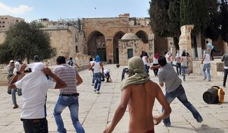 ** FILE ** Archive photo of men throwing stones on the Temple Mount. (Associated Press)
