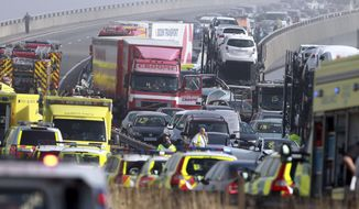 Emergency vehicles attend the scene of a major accident on the Sheppey Bridge Crossing near Sheerness in Kent, south England, following a multi-vehicle collision earlier Thursday morning, Sept. 5, 2013.  (AP Photo/Gareth Fuller, PA)