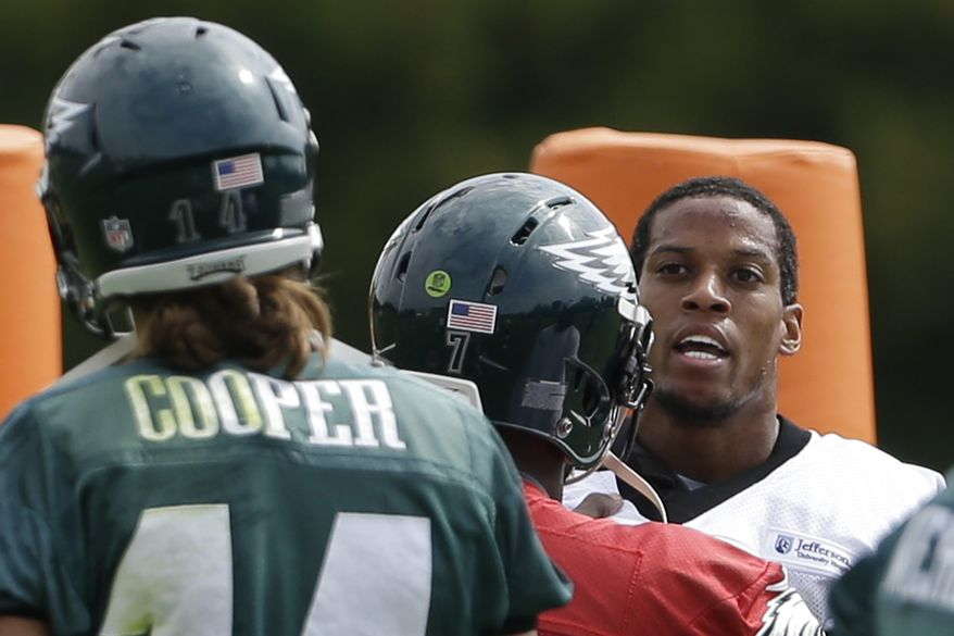 Philadelphia Eagles quarterback Michael Vick, center, restrains Cary Williams from Riley Cooper (14), during practice at the NFL football team's training facility, Thursday, Sept. 5, 2013, in Philadelphia. (AP Photo/Matt Rourke)