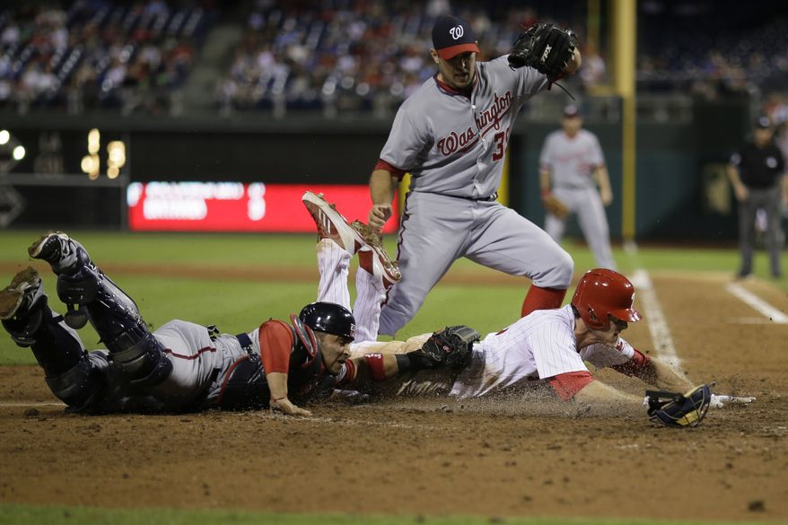 Washington Nationals catcher Jhonatan Solano dives to tag Phillies second baseman Chase Utley as Craig Stammen tries to avoid a collision. (Associated Press photo)