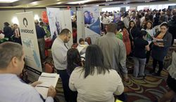 Job seekers check out companies at a job fair in Miami Lakes, Fla., on Wednesday, Aug. 14, 2013. (AP Photo/Alan Diaz)