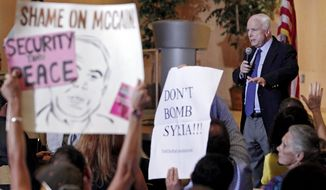 Members of the crowd hold up signs against military action in Syria as U.S. Sen. John McCain, R-Ariz., speaks with constituents during a town hall meeting at the Burton Barr Central Library, Thursday, Sept. 5, 2013, in Phoenix. The meeting, which was supposed to host a variety of topics that effect Arizonans, became a platform for the topic of military action in Syria. (AP Photo/Ralph Freso)