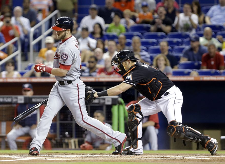 Miami Marlins catcher Jeff Mathis tags Washington Nationals' Bryce Harper, left, after he struck out swinging during the first inning of a baseball game, Friday, Sept. 6, 2013, in Miami. (AP Photo/Wilfredo Lee)