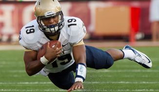 Navy quarterback Keenan Reynolds (19) stumbles during a run up field against Indiana during the first half of an NCAA college football game, Saturday, Sept. 7, 2013, in Bloomington, Ind. (AP Photo/Doug McSchooler)
