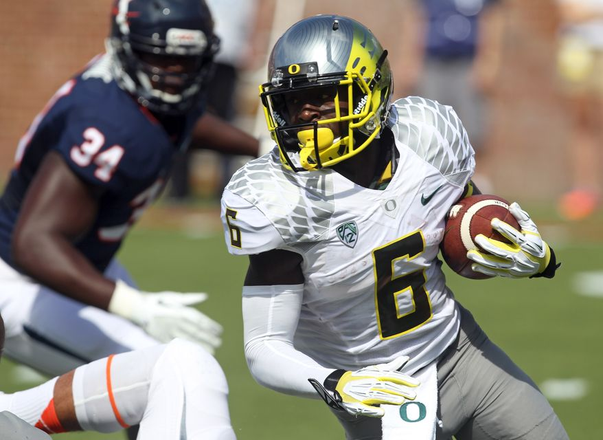 Oregon running back De'Anthony Thomas (6) runs past Virginia linebacker Kwontie Moore (34) during the first half of an NCAA college football game at Scott Stadium, Saturday, Sept. 7, 2013, in Charlottesville, Va. (AP Photo/Andrew Shurtleff)