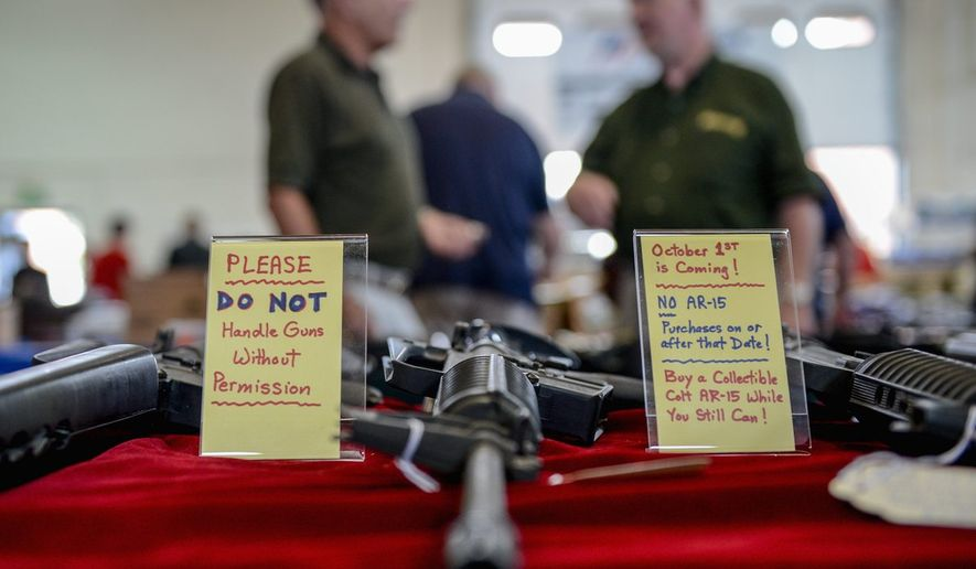 "** FILE ** In this Sept. 8, 2013, file photo, a sign warning of the coming assault weapons ban in Maryland is next to AR-15 semi-automatic rifles at the Annapolis Gun Show. ""You see people who've bought guns, you see older people. This is not about what everybody thinks it is. This is a plan to disarm America,"" said Neil Kravitz of Appalachian Promotions. (Andrew Harnik/The Washington Times)"