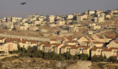 ** FILE ** The Jewish neighborhood of Pisgat Zeev is pictured in east Jerusalem in 2009, with the Shuafat refugee camp in the background and Israel's separation barrier running between them. (AP Photo/Sebastian Scheiner)