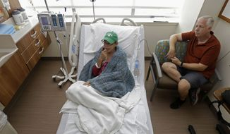 Bev Veals (left), accompanied by her husband, Scott, undergoes chemotherapy treatment at Duke Cancer Center in Durham, N.C., on Tuesday, Aug. 27, 2013. (AP Photo/Gerry Broome)