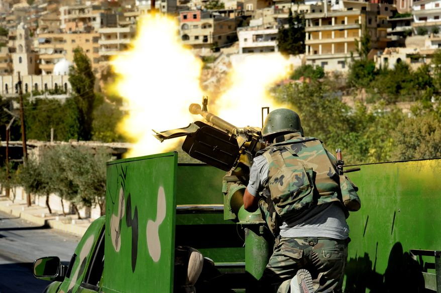 **FILE** In this photo released by the Syrian official news agency SANA, a Syrian military solider fires a heavy machine gun during clashes with rebels in Maaloula village, northeast of the capital Damascus, Syria, on Sept. 7, 2013. (Associated Press)