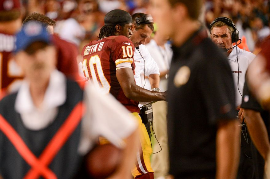 Washington Redskins quarterback Robert Griffin III (10) talks with Washington Redskins offensive coordinator Kyle Shanahan on the sideline in the third quarter as the Washington Redskins play the Philadelphia Eagles in Monday Night NFL football at FedExField, Landover, Md., Monday, September 9, 2013. (Andrew Harnik/The Washington Times)