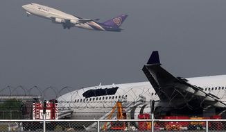 A Thai Airways passenger plane takes off over a damaged Thai Airways Airbus A330-300 at Suvarnabhumi International Airport in Bangkok, Thailand Monday, Sept. 9, 2013. (AP Photo/Apichart Weerawong)