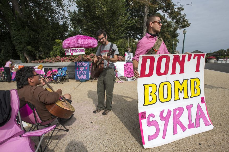 Peace activists opposed to American intervention in Syria, gather on a street corner at the U.S. Capitol in Washington on Sept. 9, 2013. As Congress returns to work from August recess, President Obama is seeking authorization from Congress for a military strike against Syria in response to the use of chemical weapons in the civil war there. (Associated Press)