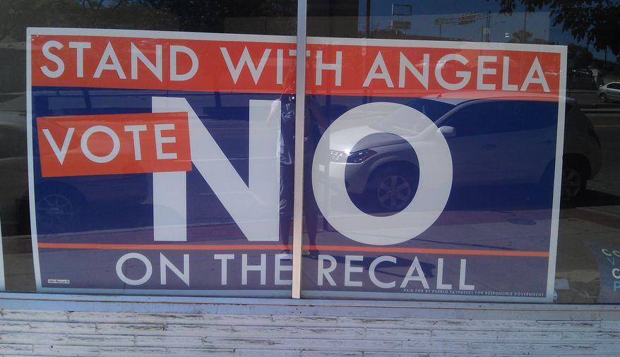 A sign outside state Sen. Angela Giron's campaign headquarters in Pueblo, Colo., urges voters to oppose the recall. (Valerie Richardson/The Washington Times)