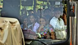 ** FILE ** Indian passengers riding on a public bus look toward a court complex crowded with media personnel awaiting a verdict in the Dec. 16, 2012, gang rape case, in New Delhi, India. (AP Photo/Manish Swarup)