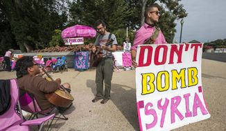 Peace activists opposed to American intervention in Syria, gather on a street corner at the U.S. Capitol in Washington, Monday, Sept. 9, 2013. (AP Photo/J. Scott Applewhite)