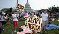 "** FILE ** Linda Norman (right) and Joanna Galt, both from Florida, hold their banners during a ""Exempt America from Obamacare"" rally on the West Lawn of the Capitol in Washington on Sept. 10, 2013. (Associated Press)"