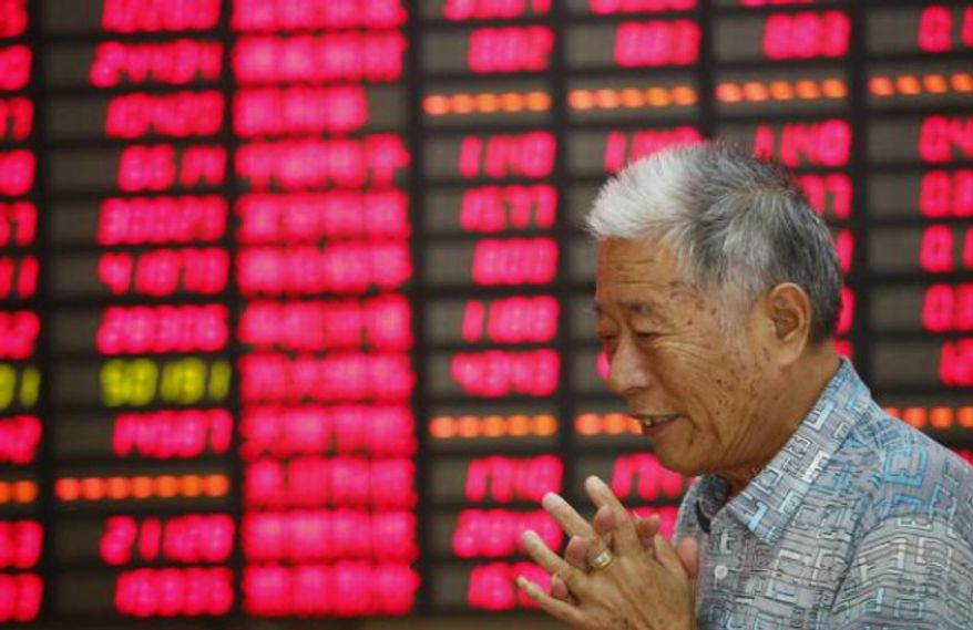 An investor looks at the stock price monitor at a private securities company Aug. 19, 2013 in Shanghai, China. (Associated Press) ** FILE **