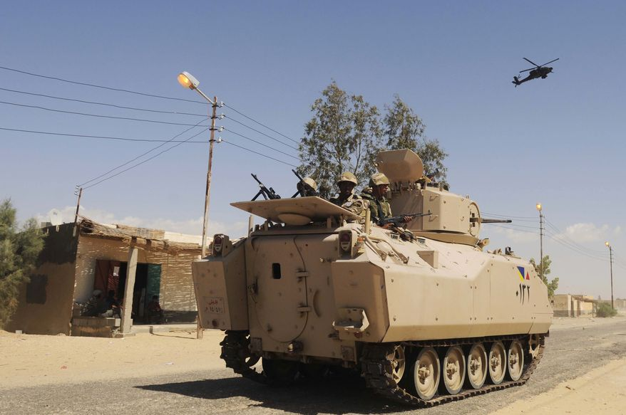 ** FILE ** In this Tuesday, May 21, 2013, file photo, Egyptian Army soldiers patrol in an armored vehicle backed by a helicopter gunship during a sweep through villages in Sheikh Zuweyid, northern Sinai, Egypt. (AP Photo, File)