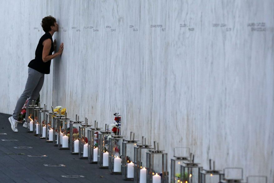 A visitor kisses a name on the wall containing the 40 names of the crew and passengers of Flight 93 at the Flight 93 National Memorial during a candlelight remembrance on Tuesday, Sept. 10, 2013. (AP Photo/Gene J. Puskar)