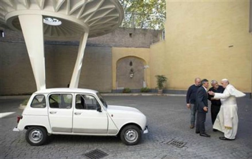 Pope Francis, right, speaks with Rev. Renzo Zocca, second from right, and owner of the Renault 4L seen at left, his assistant Luigi Macchioni, and car-body repairer Stefano Veronesi, fourth from right, after he was donated the car by Zocca, at the Vatican, Sept. 7, 2013. Rev. (AP Photo/L'Osservatore Romano, ho)