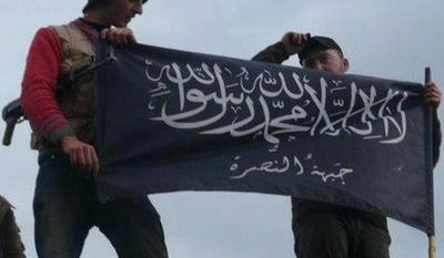 **FILE** Rebels from al Qaeda-affiliated Jabhat al-Nusra wave their brigade flag on Jan. 11, 2013, as they step on the top of a Syrian air force helicopter at a Taftanaz air base in Idlib province in northern Syria that was captured by the rebels. (Associated Press/Edlib News Network)